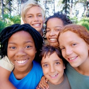 A closeup of image of a group of kids smiling at the camera while standing in the woods