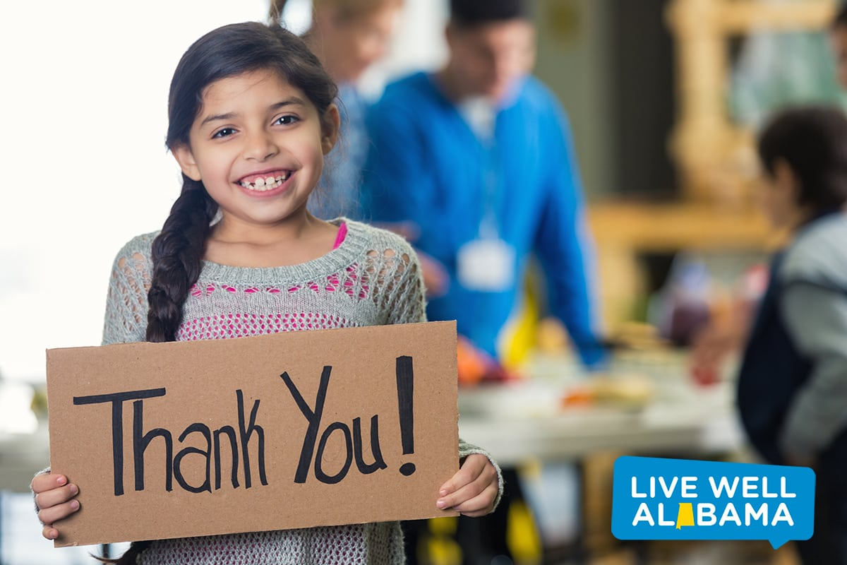 emergency food. Hispanic girl is holding a cardboard sign with 'Thank You!' written on the board. She and her family are in a soup kitchen or food bank. She is smiling at the camera. Her brown hair is in a braid. Volunteers are serving her family in the background. Focus is on the girl and the sign.