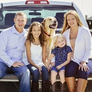 Caucasian family and dog sitting in truck bed on farm
