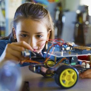 Pre-adolescent girl assembling robotics in classroom