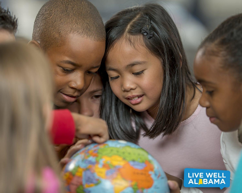 USDA Nondiscrimination Statement. Students surrounding globe on desk.