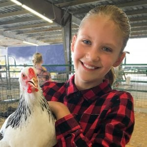 smiling girl holding a chicken