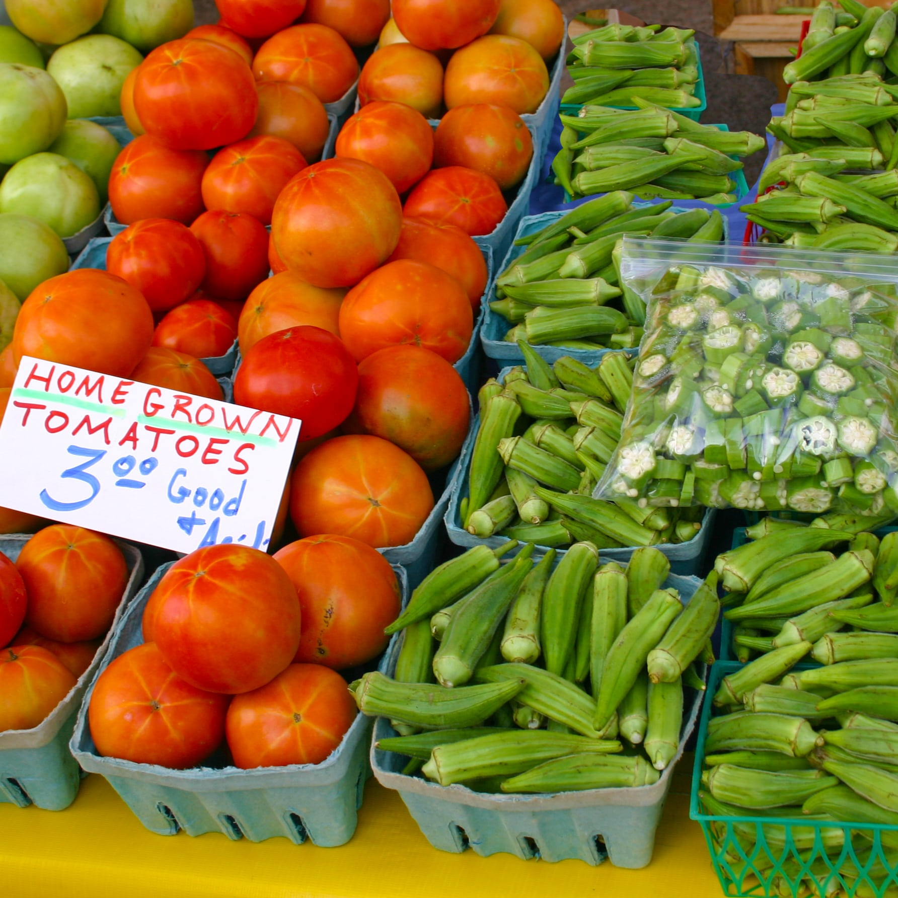 fresh tomatoes and okra in baskets for sale at a fresh vegetable stand