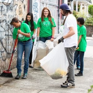 group of 4-H'ers picking up trash and sweeping a walkway