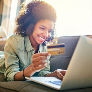 cheerful woman working on a laptop with a credit card in hand