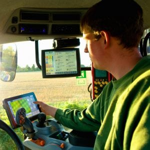 Young man driving tractor using touchscreen on global positioning system