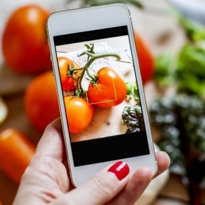 Woman photographing vegetables with a cell phone