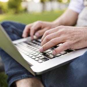 man sitting on grass working on a laptop