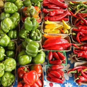 variety of red, yellow, and green peppers in baskets