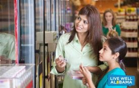 Mother and daughter shopping with coupons at the grocery store.
