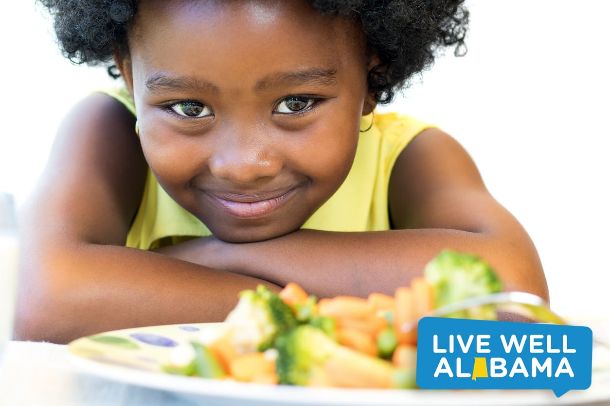 African American kid in front of plate of vegetables