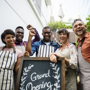 "Culturally diverse small business owners proudly standing by ""Grand Opening"" Sign"
