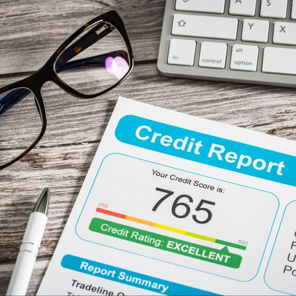 Credit report on a desk beside a pair of glasses and computer keyboard.