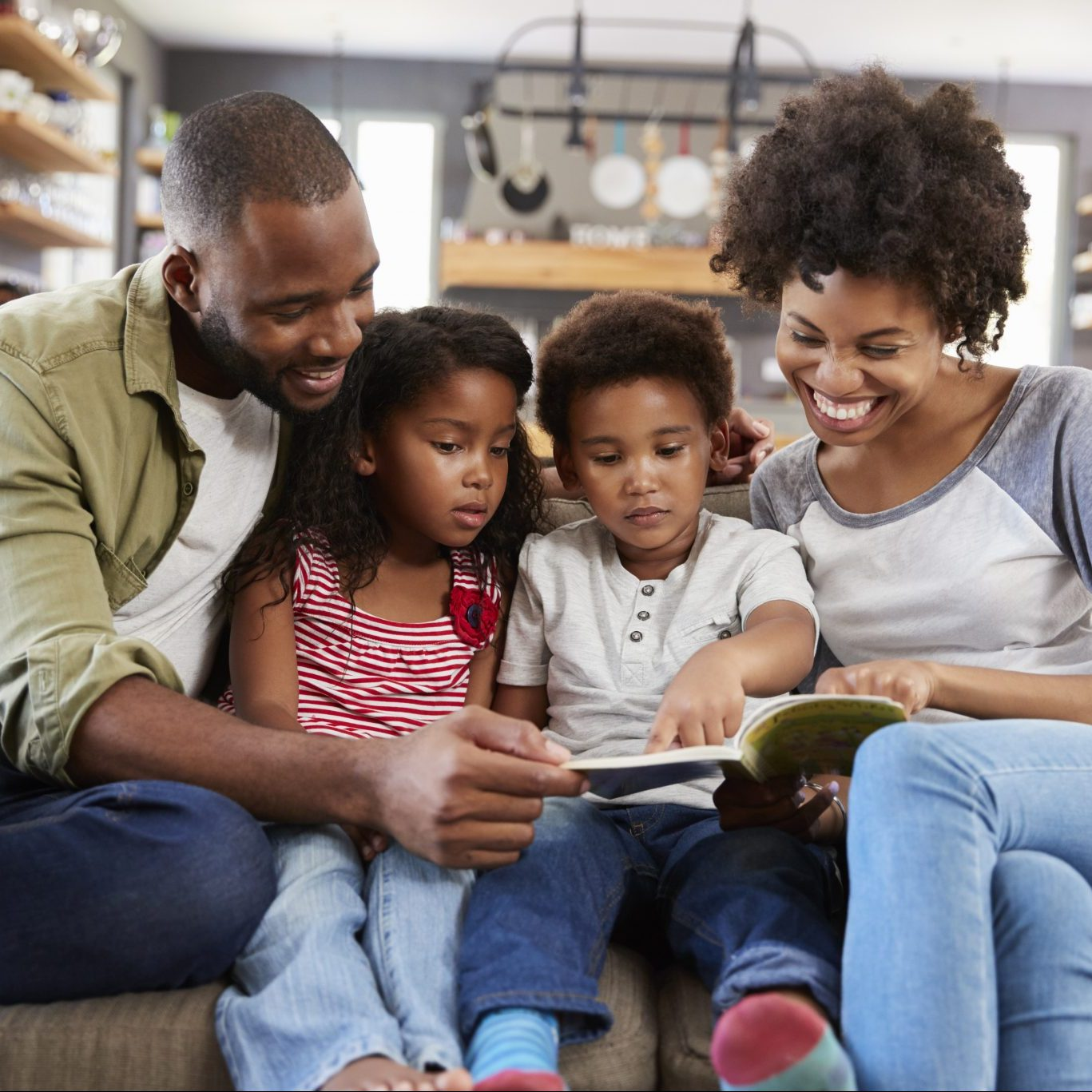 Mom and dad with two young children sitting on sofa reading a book together