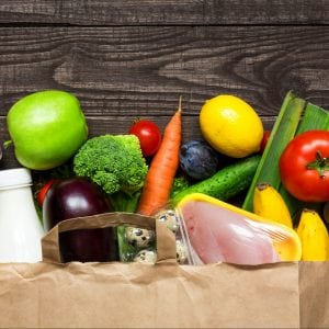 Paper grocery bag full of different healthy food: Vegetables, dairy, meats, breads