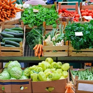 Fresh fruits and vegetables in wooden crates for sale at a farmers market