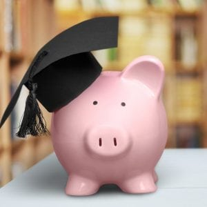 Piggy Bank with Graduation Hat on with books in the background to illustrate financial literacy.