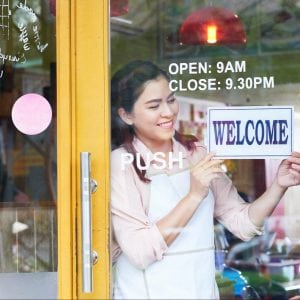 Smiling Latino bakery owner hanging welcome sign on the door