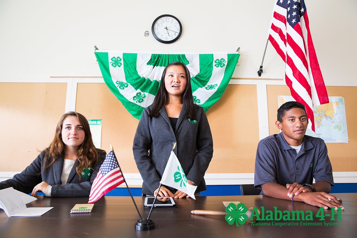Three youth behind a desk with banners and national flag; Alabama 4-H
