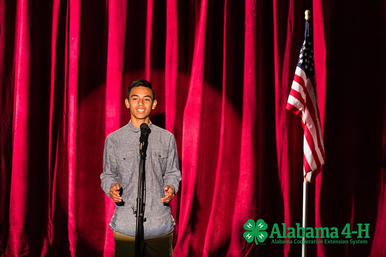 4-H member speaking on stage; Alabama 4-H