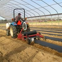 A farmer lays plasticulture within the frame of this high tunnel.