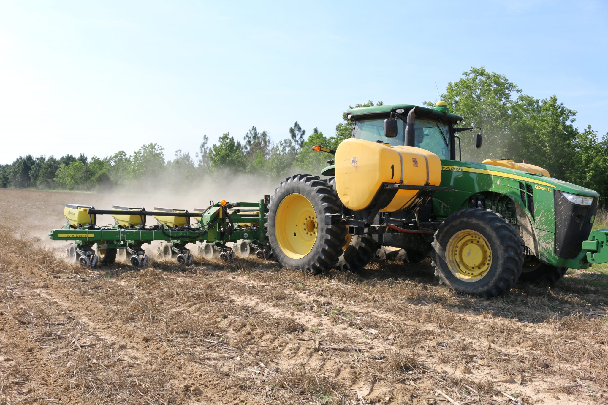 A tractor planting row crops.