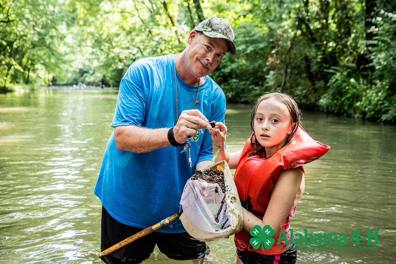 Alabama 4-H volunteer and member in creek during lesson