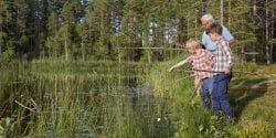 Grandfather teaching grandsons fishing at sunny lakeside