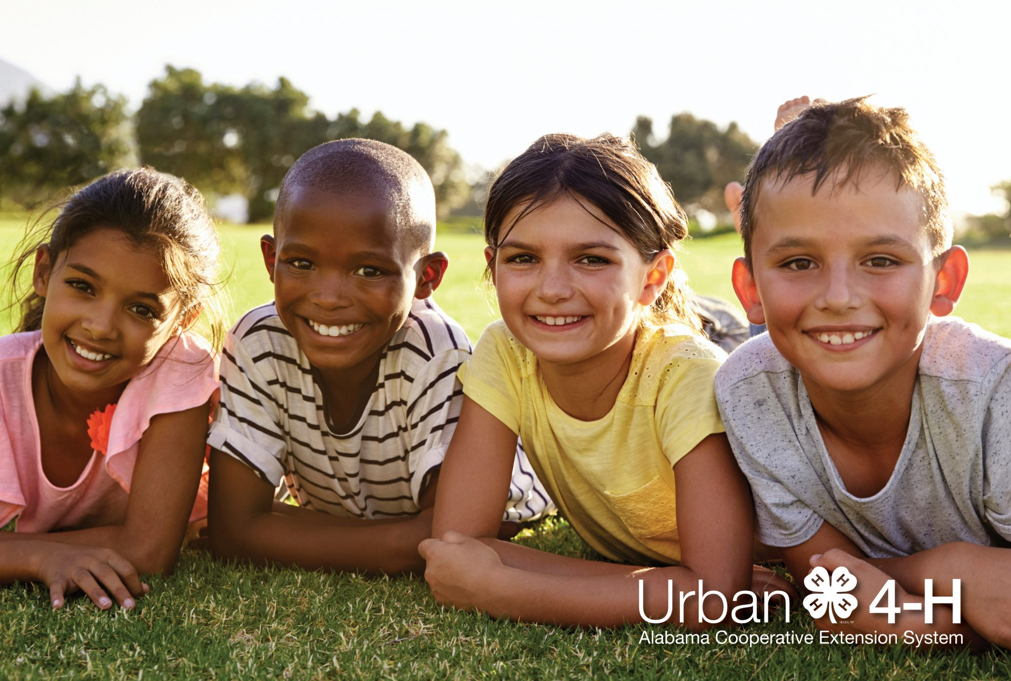 Four elementary aged children, multi-ethnic, lying on the grass smiling outside.