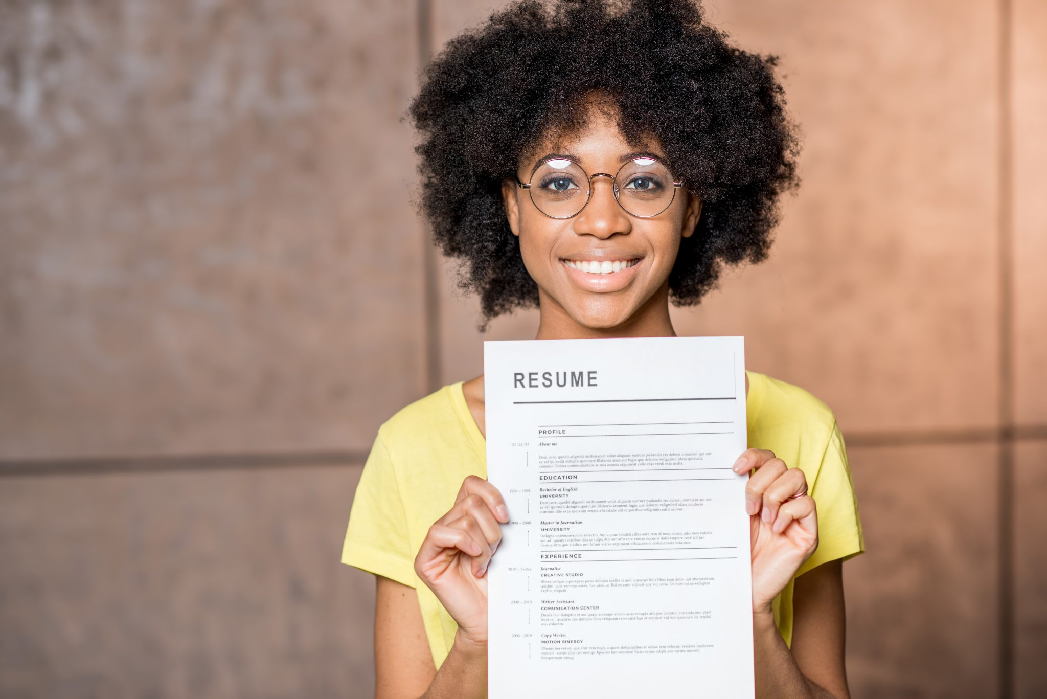 Portrait of a young African woman holding resume document indoors
