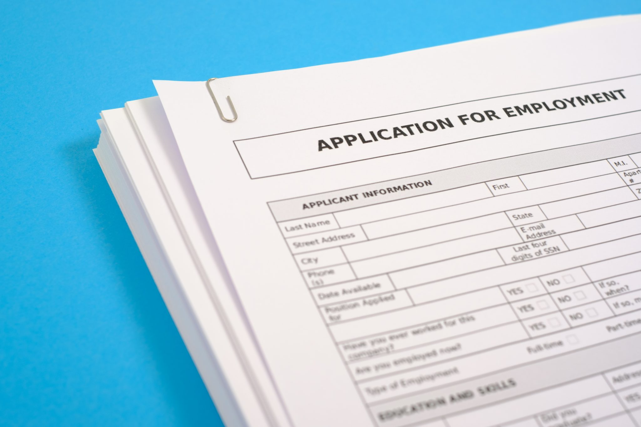 Stack of cv and application for employment on blue desk