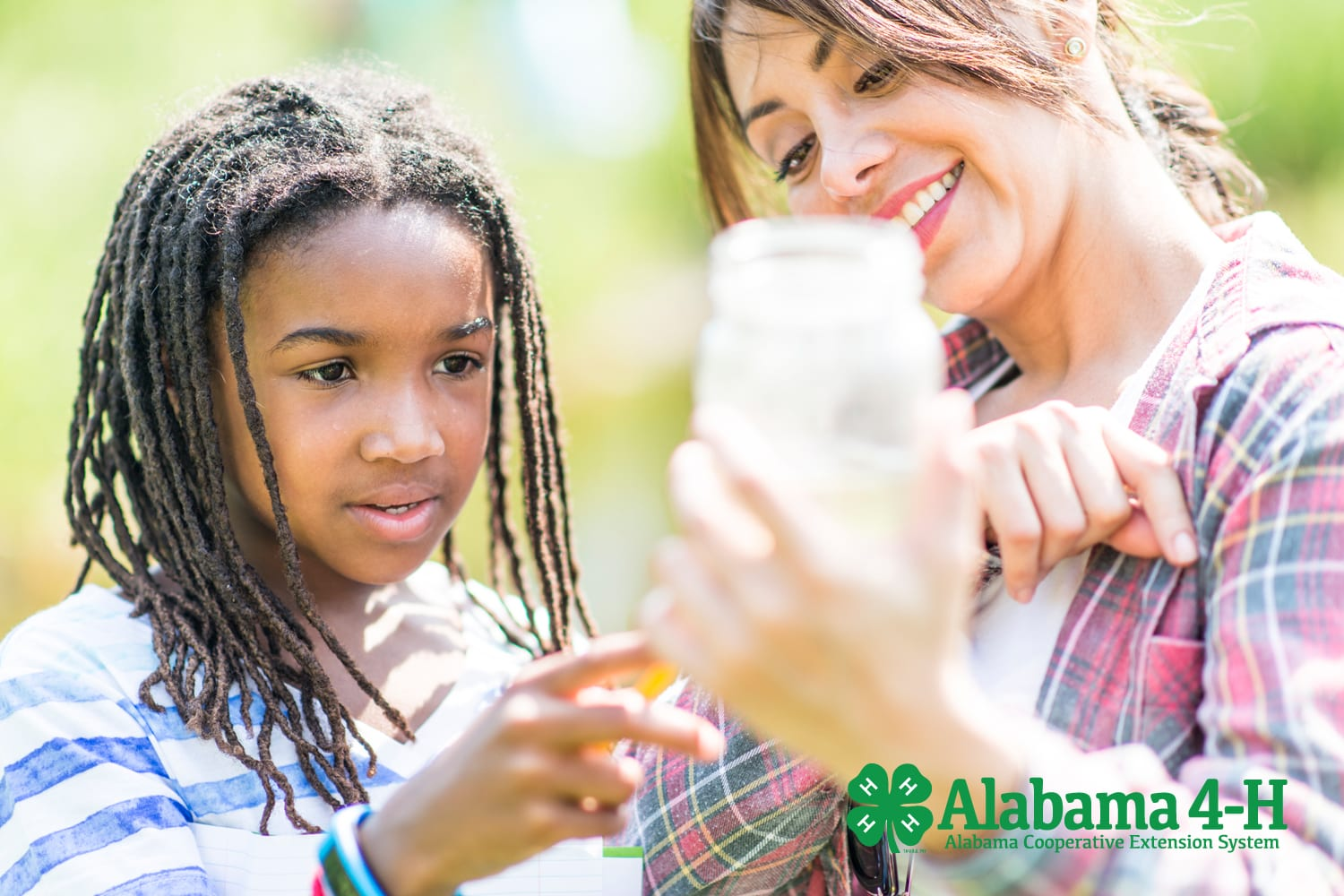 Alabama 4-H volunteer outdoors with 4-H member monitoring water quality