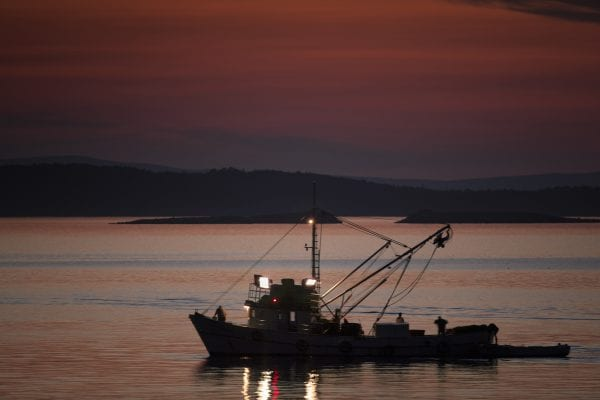 A fishing boat silhouette against a glorious orange sunset on the ocean.