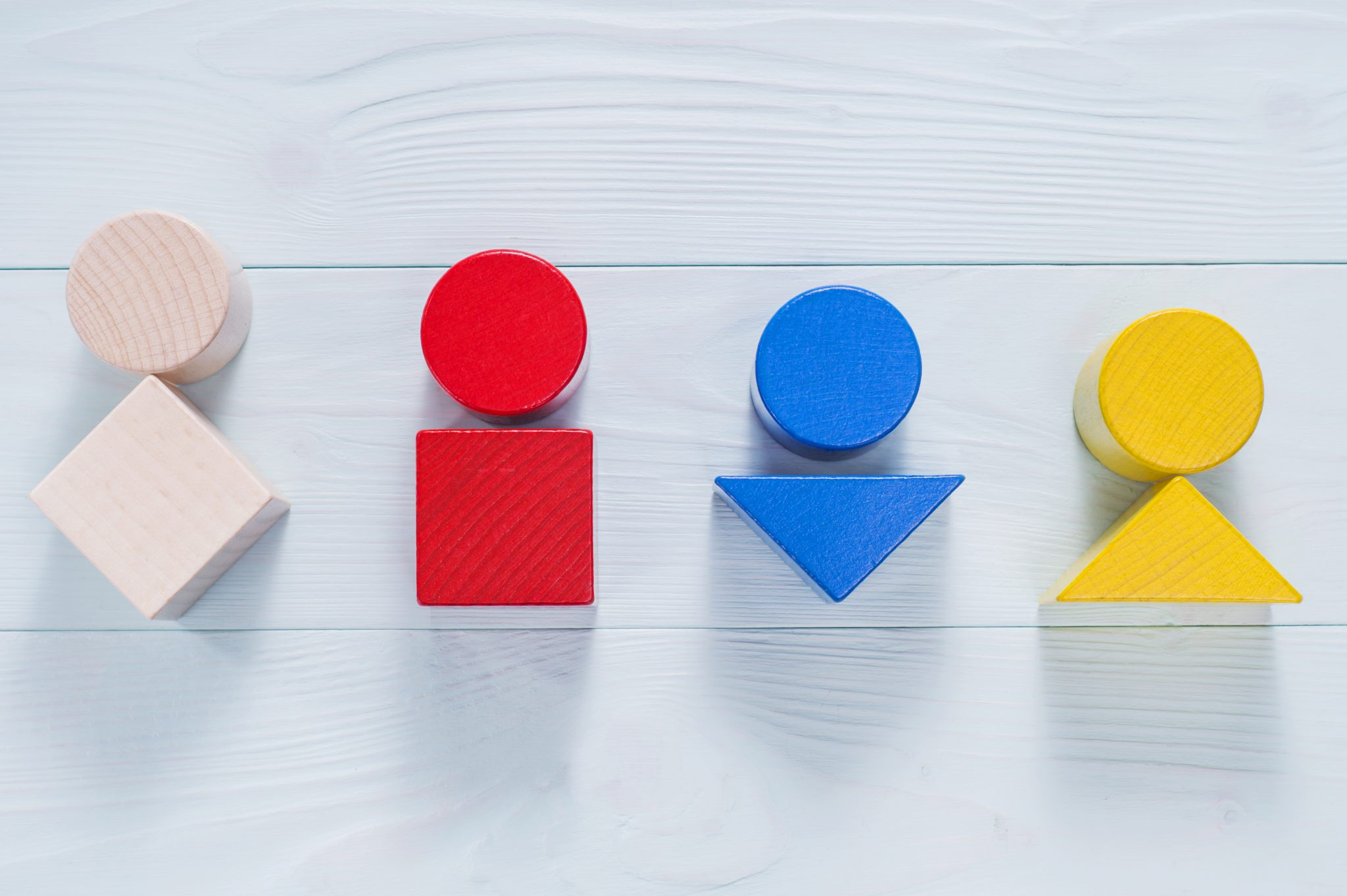 Wooden blocks, circle, triangle, square, arranged to depict body types.