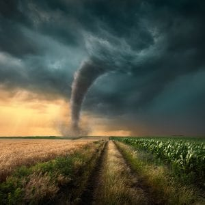 Tornado in agricultural field at sunset