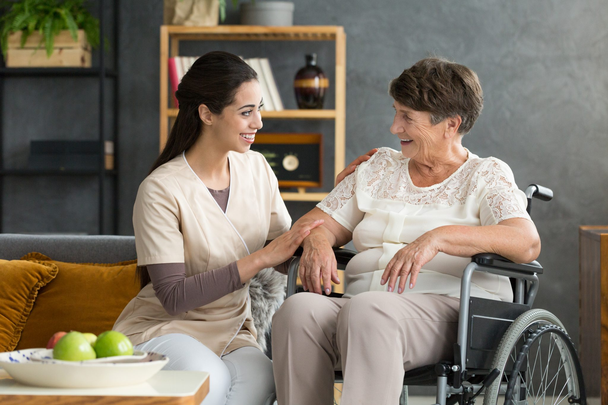 Elderly woman in a wheelchair in her livingroom meeting with visiting nurses aid.