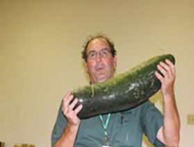 Robert Spencer holding large bottle gourd. Gourd seems to be over two feet long