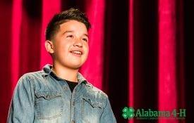 Alabama 4-H Junior Achievement; young boy speaking on stage