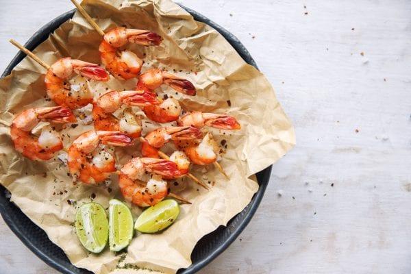 Grilled shrimps on skews with lime slices