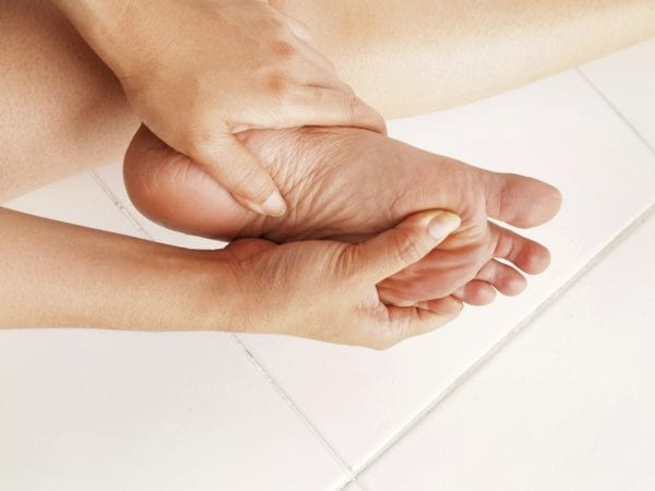 woman checks her aching foot