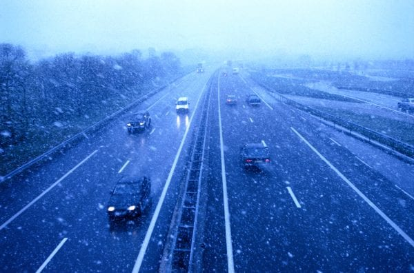 high angle view of traffic driving on a freeway in snowfall