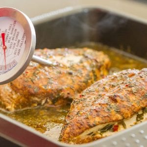 The temperature being measured of two seasoned chicken breasts in a baking tray.
