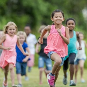 A multi-ethnic group of elementary age children are playing together outside at recess