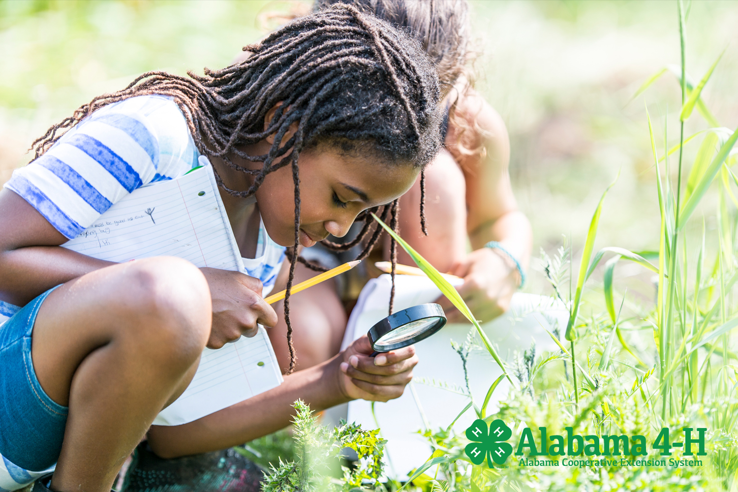 Alabama 4-H Project WILD 4-H member looking through magnifying glass