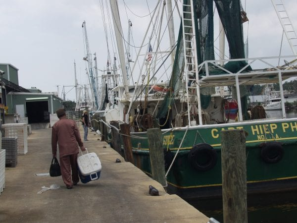 Workers walking on dock beside shrimp boats