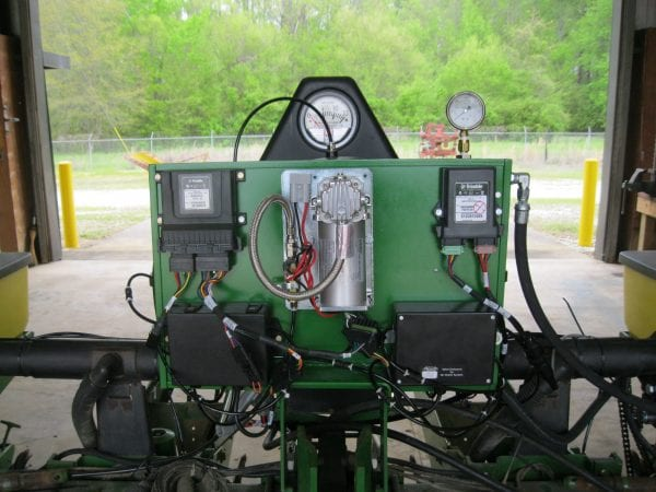 A Trimble air clutch control setup. In the center of this panel is the air compressor with the associated storage (not visible) mounted on the back side. The bottom two black boxes on the left and right are air valve modules used to directly disengage clutches when pressure is applied to the connecting lines. Each air valve module controls up to 4 sections or individual rows. The final component is the ECU on the upper left of the panel. This communicates information between the air valve modules and in-cab display.