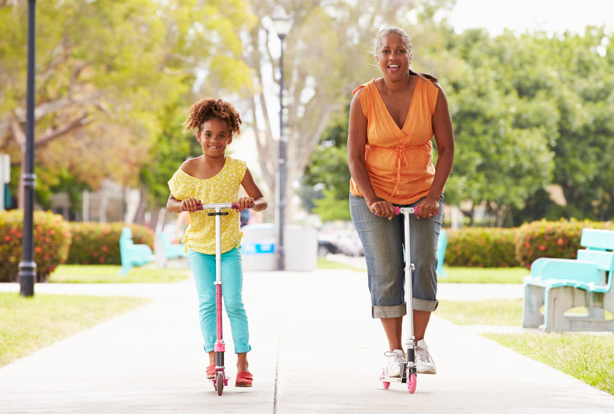 Grandmother and granddaughter get some exercise by scootering in the park.