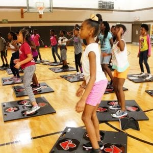 A group of school-age children are in a gym exercising with the TEEN exergame.