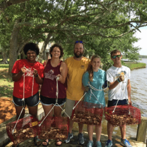 Group of people holding nets filled with oysters