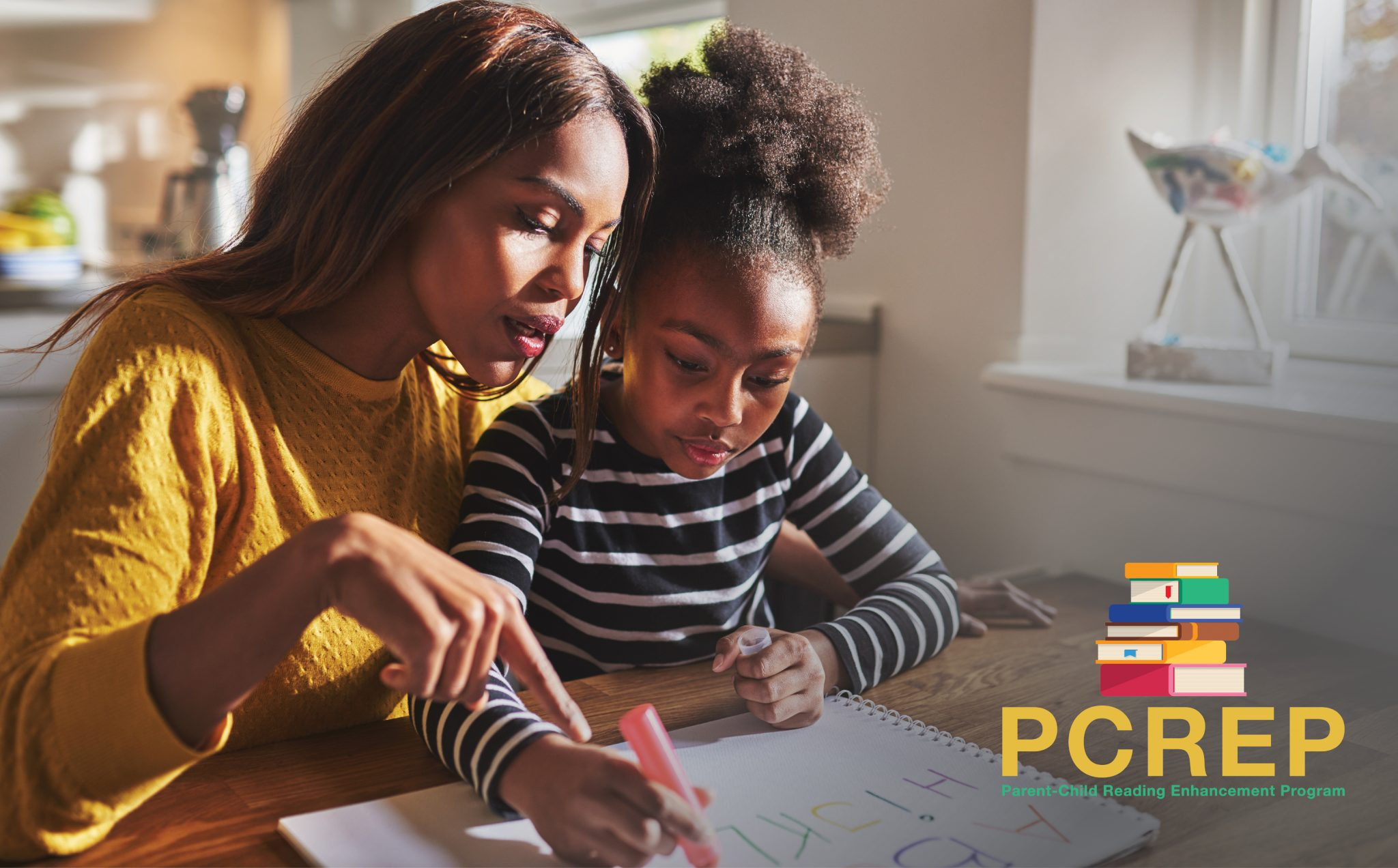 African American mother and child sit at the dining room table writing the alphabet